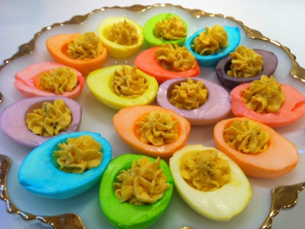 Cut the eggs in half, placing the cooked yolk into a bowl to make your deviled egg filling. Make your dye, using one coffee cup for each color you want to do. I used McCormick food coloring and followed the instructions on the package to make blue, green, rose and .